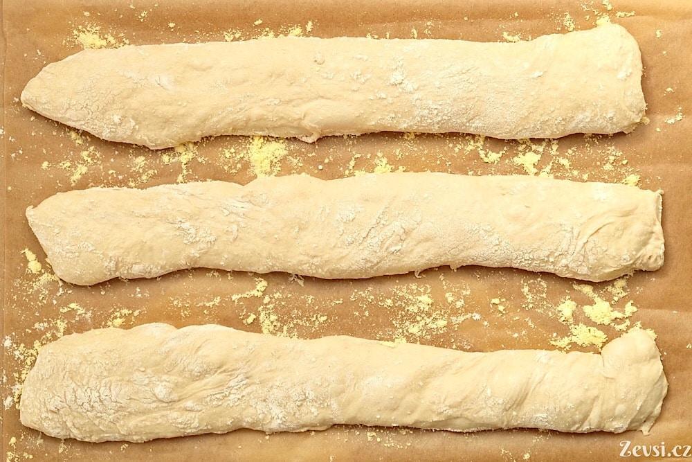 Bagety na pečicím papíře posypaném moukou.